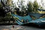 Settler kids play on a fallen sunshade, in the unauthorized Israeli outpost of Chavat Ma'on, West Bank.