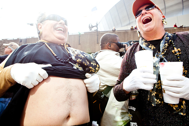 A Saints fan pulls up his dress to show off the fleur de lis shaved into his stomach at the parade in Buddy D's honor on January 31, 2010 in New Orleans.<br /> <br /> Thousands of Saints fans wearing dresses paraded from the Louisiana Superdome to the French Quarter to honor a promise made by the late sportscaster and Saints super-fan Buddy Diliberto aka &quot;Buddy D&quot;.<br /> <br /> In 1993 Buddy D, who passed away in 2005, remarked on air that if the Saints were to make it to the Super Bowl, he would wear a dress and dance down the streets.  The comment was repeated at various times and never forgotten by his listeners.<br /> <br /> Led by former New Orleans Saints quarterback Bobby Hebert, who has taken Buddy D's place on WWL radio, thousands made good on his promise for him, dancing, drinking, and cavorting their way down the street, alternately yelling out &quot;Who Dat!&quot; and &quot;Buddy D!&quot; in front of an onlooking crowd an estimated 85,000 people strong.<br /> <br /> The hard luck NFL team the New Orleans Saints has reached its first Super Bowl in team history, after 43 years largely filled with losing seasons and futility.  It is difficult to travel anywhere in the area without some reminder of this fact, as the team and city are intertwined perhaps like no other sports franchise in this country.