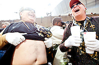 "A Saints fan pulls up his dress to show off the fleur de lis shaved into his stomach at the parade in Buddy D's honor on January 31, 2010 in New Orleans.<br /> <br /> Thousands of Saints fans wearing dresses paraded from the Louisiana Superdome to the French Quarter to honor a promise made by the late sportscaster and Saints super-fan Buddy Diliberto aka ""Buddy D"".<br /> <br /> In 1993 Buddy D, who passed away in 2005, remarked on air that if the Saints were to make it to the Super Bowl, he would wear a dress and dance down the streets.  The comment was repeated at various times and never forgotten by his listeners.<br /> <br /> Led by former New Orleans Saints quarterback Bobby Hebert, who has taken Buddy D's place on WWL radio, thousands made good on his promise for him, dancing, drinking, and cavorting their way down the street, alternately yelling out ""Who Dat!"" and ""Buddy D!"" in front of an onlooking crowd an estimated 85,000 people strong.<br /> <br /> The hard luck NFL team the New Orleans Saints has reached its first Super Bowl in team history, after 43 years largely filled with losing seasons and futility.  It is difficult to travel anywhere in the area without some reminder of this fact, as the team and city are intertwined perhaps like no other sports franchise in this country."