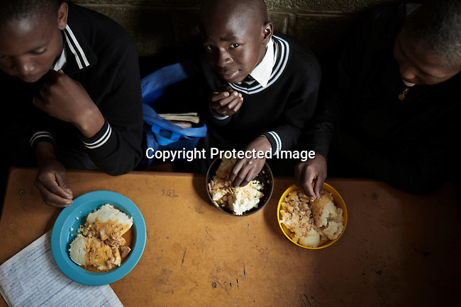 MASERU, LESOTHO SEPTEMBER 1: Children eat lunch  in a classroom at Masapong primary school on September 1 in Masapong district outside Maseru, Lesotho. The are given two meals a day, usually pap and fish by the World Food Program (WFP).  (Photo by: Per-Anders Pettersson)