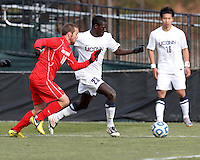 University of Connecticut forward Mamadou Diouf (23) dribbles down the wing as University of New Mexico midfielder Levi Rossi (16) defends..NCAA Tournament. With a goal in the second overtime, University of Connecticut (white) defeated University of New Mexico (red), 2-1, at Morrone Stadium at University of Connecticut on November 25, 2012.