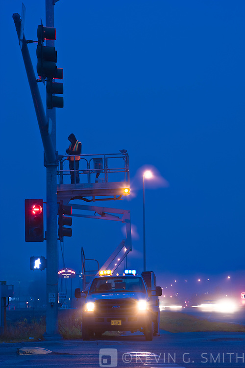 Worker in a man-lift above a busy intersection repairing a traffic light just before dawn, fog, blurrred car lights, Anchorage, Southcentral Alaska, USA. Not Model Released