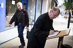 © Joel Goodman - 07973 332324 . 02/09/2013 . Bury , UK . A priest signs the book of condolences which is placed on the streets of Bury Town Centre . The funeral of fireman Stephen Hunt at Bury Parish Church today (Tuesday 3rd September 2013) . Stephen Hunt died whilst tackling a blaze at Paul's Hair World in Manchester City Centre in July 2013 . Photo credit : Joel Goodman