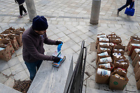 Volunteers move bags of nonperishable food and supplies into a Belmont Council on Aging bus as part of distribution to senior citizens in need by the Belmont Food Pantry in Belmont, Massachusetts, on Sat., March 21, 2020. As part of the response to the ongoing Coronavirus (COVID-19) global pandemic, the Belmont Food Pantry arranged for curbside pickup to minimize person-to-person contact. Each pair of bags included a variety of nonperishable food, including some canned meats, and toilet paper and paper towels. The Food Pantry usually purchases food directly from grocers and food providers for distribution, but because of ongoing shortages, the Food Pantry received donations from the Greater Boston Food Bank in order to keep up with ongoing food distribution. For the senior citizens, the Pantry decided it was safer to bring food to those in need rather than ask them to pick it up as usual.