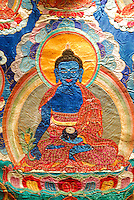 Ancient silk embroidered thangka of the Medicine Buddha, Sangye Menla, his left hand holding a begging bowl full of long-life nectar, right hand holding the blooming myrobalan plant capable of healing passion, aggression and ignorance, the causes of all illness, Tibet Museum, Lhasa, China.