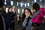 A woman greets a little girl with a kiss on the hand during the Easter Sunday service at restored Surp Giragos Armenian Church, in Diyarbakir, Turkey, April 5, 2015. The church has no regular services, nor a priest of its own, so Father Sevan Civanoglu came from Istanbul to officiate. Surp Giragos was one of 13 Armenian churches in Diyarbakir and the largest Armenian church in the Middle East. Beginning in 1915, the Armenian Genocide sharply reduced Diyarbakir's Armenian population, and many surviving Armenians left the city or were converted to Islam. By the early 1990's, the church had fallen into disrepair. In 2009, Armenians living in Istanbul formed a foundation to restore Surp Giragos, funded mostly by private donations from the Armenian diaspora. It reopened in 2011, but the Armenian community, still in the process of its own resurrection, remains small. <br /> The 100th anniversary of the Armenian Genocide will be commemorated on April 24, 2015. The Turkish government still refuses to acknowledge genocide--the systematic killing of roughly 1.5 million Armenians from 1915-1923--but Kurds in the Southeast, even some whose ancestors took part in the killing, speak openly and express remorse about what happened.