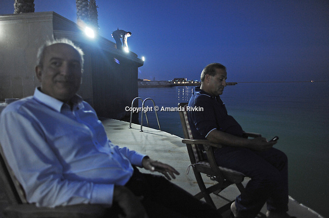 Ibrahim Ibrahimov sits down after dinner by the Caspian Sea with a Turkish business associate, M. Tayfur Ozturk at the edge of his home between Sangachal and Sahil, Azerbaijan on August 16, 2012.