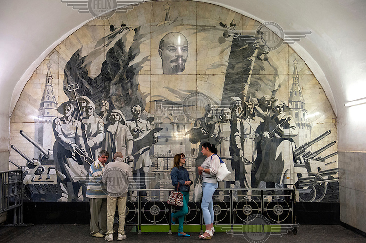 Passengers stand infront of a mural depicting Soviet heros at Novokuznetskaya Metro Station. Opened in 1943 its murals feature battles, military figures and the workers of the Great Patriotic War (World War 2). It also uses white SIberian marble for its facing.