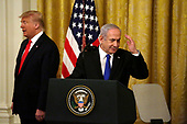 Israel's Prime Minister Benjamin Netanyahu salutes as United States President Donald J. Trump looks on during a meeting in the East Room of the White House in Washington, D.C.,on Tuesday, January 28, 2020. Credit: Joshua Lott / CNP
