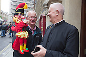 Covent Garden, London, UK. 11 May 2014. The festival starts with a procession around the streets of Covent Garden. Mr Punch meets a priest. The Covent Garden May Fayre and Puppet Festival takes place at St Paul's Church.