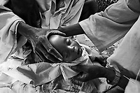 Farchana, Tchad, June 5, 2004.Men prepare for burial the body of Hafiz Malik Yaya, 9 months old, who died of severe malnutrition. More than 13 thousand Sudanese refugees from Darfur stay in this camp in very harsh conditions.
