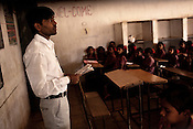 A teacher teaches in a classroom in a government run school in Caregaon, Thane, Maharashtra. These schools run a specially designed concept of 'aflatoon' as part of the curriculam whereby students are made aware of their child as described in the convention of rights of child. These students are made aware of right to survival, right to protection, right to development and right to participation.