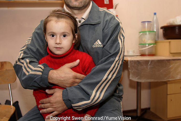 Chechen Man with his 5-years old daughter..He use to live in the bombed house in Grozny for 6 years together with is wife, daughter and aunt..He succeed to survive over 10 years of Chechen war, but in September 2005 the raids of dressed in cowl policemen or soldiers of Russian forces  visiting him at his place, threating him and his family life, put him to flight. They arrived in URiC Wola Center in Warsaw in the middle October..-For security reason, the face of the adult asylum seeker have been evicted of the photography..-For security reason, the names of the adult asylum seeker have been change. .-Article 9 of the Act of 13 June 2003 on grating protection on the Polish territory (Journal of Laws, No 128, it. 1176) personal data of refugees are an object of particular protection..-Cases where publication of a picture or name of asylum seeker had dramatic consequences for this persons and is family back in Chechnya. .Please have safety of those people in mind. Thank you.