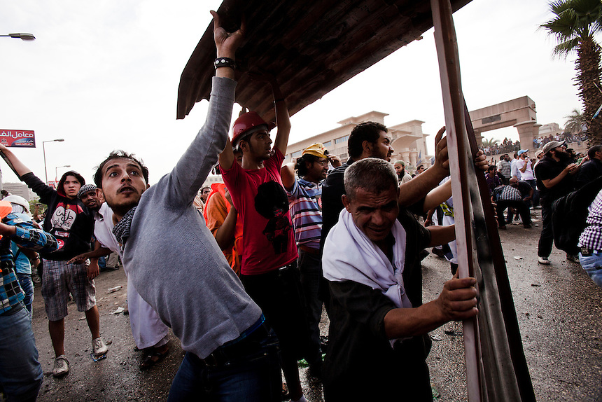 An Egyptian protester throws a stone during violent clashes between protesters and Military Police in front of the Egyptian Ministry of Defense in central Cairo's suburb of Abbaseya, March 4, 2012. Protesters marched on the MOD to demonstrate against over 20 deaths during a sit-in protest two days before. Photo: Ed Giles.