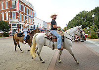 NWA Democrat-Gazette/BEN GOFF &bull; @NWABENGOFF<br /> Quinn Simmons and Tommy Garrett ride horseback past the Bentonville square on Sunday Aug. 16, 2015 after stopping for a milkshake at the Walmart Museum's Spark Cafe. The pair said they live nearby and wanted to take their horses for a short ride around town.