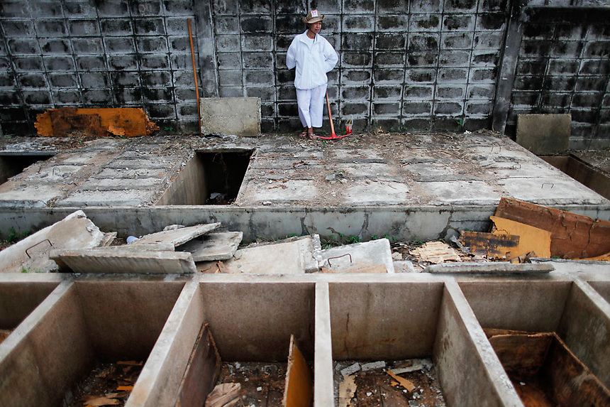 A woman stands behind open graves after unclaimed bodies were taken out during a Thai Chinese ceremony at the Mang Teung Sua Jung Cemetery in Chonburi province southeast of Bangkok March 18, 2012. Every 10 years, hundreds of people wearing white, a customary colour for funerals and visiting temples, gather at this cemetery to exhume and cremate corpses as they believe they are helping the dead who have no friends or relatives. The ashes of the unclaimed bodies are spread on the sea to make room at the burial ground for more unclaimed bodies in the coming years. The tradition originated 90 years ago after diseases like Malaria killed many Thais of Chinese descent living in Chonburi.  REUTERS/Damir Sagolj (THAILAND)