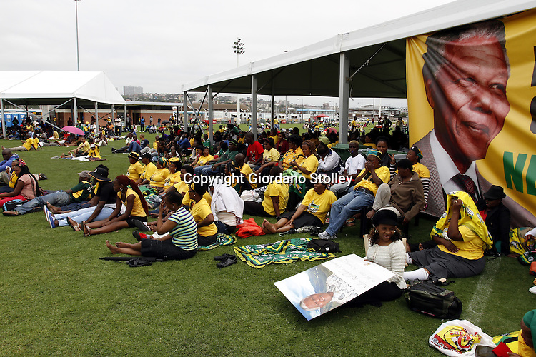DURBAN - 15 December 2013 - Mourners watch the funeral of Nelson Mandela in the Peoples Park outside the Moses Mabhida Stadium in Durban as it was broadcast live on big screens from Qunu where the international icon was laid to rest. Picture: Allied Picture Press/APP
