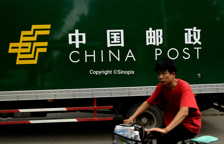 A man rides a bicycle past a China Post truck in Beijing, China..