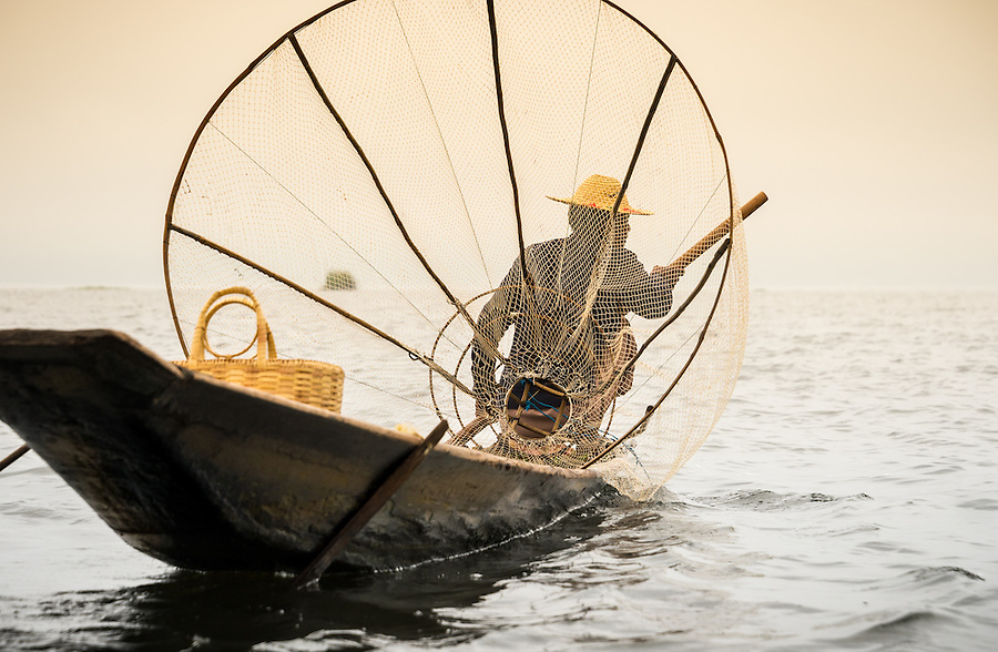 INLE LAKE, MYANMAR - CIRCA DECEMBER 2013: Fisherman with typical net and boat in the Inle Lake, Myanmar