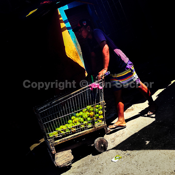 A Colombian worker pushes a customized supermarket cart, loaded with fresh limes, at the market of Bazurto in Cartagena, Colombia, 13 April 2018.
