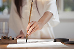 Artistic closeup of a woman Japanese sumi-e artist hand with a brush painting on rice paper in her studio wearing white