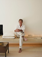 Portrait of architect John Pawson sitting on a bench in his living room