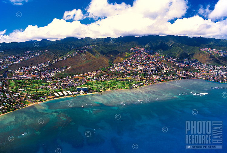 Aerial view of east Oahu coastline including the Kahala Mandarin hotel and homes on the mountain hillsides with wide sweeping ocean