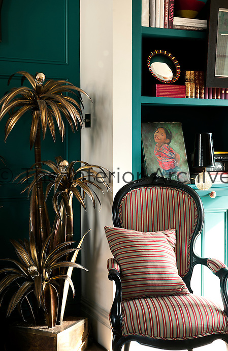 In the living room, the painted wooden panelling and bookshelves are painted in a teal colour by the Paint and Paper Library. The beautifully eccentric brass palm lights are by Maison Jansen and the late 19th century chair is covered with stripy fabric by Donghia.