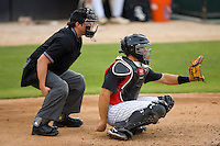 Catcher Kevin Dubler #35 of the Kannapolis Intimidators sets a target as home plate umpire Shea Gipson squats behind him during a South Atlantic League game against the Delmarva Shorebirds at Fieldcrest Cannon Stadium May 14, 2010, in Kannapolis, North Carolina.  Photo by Brian Westerholt / Four Seam Images