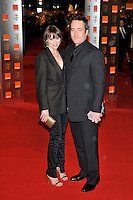 KEELEY HAWES & MATTHEW MACFADYEN.The Orange British Academy Film Awards 2009, Royal Opera House, Covent Garden, London, England, February 8th 2009..BAFTAS arrivals full length black suit tie trouser blazer jacket husband wife sandals trousers gold clutch bag .CAP/PL.©Phil Loftus/Capital Pictures