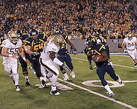 WVU running back Noel Devine heads upfield as Pitt's Greg Romeus (91) and Max Gruder (55) close in. The West Virginia Mountaineers defeated the Pittsburgh  Panthers 19-16 on November27, 2009 at Mountaineer Field at Milan Puskar Stadium, Morgantown, West Virginia.