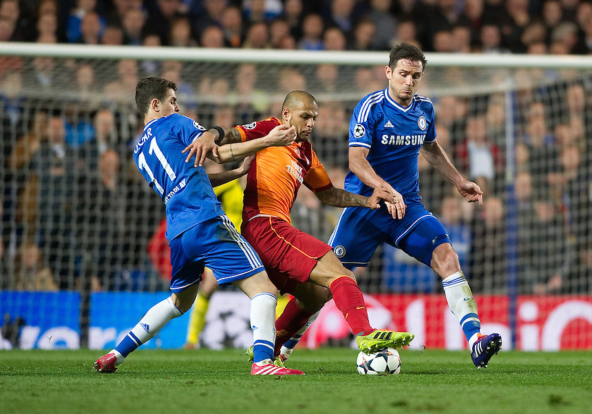 Galatasaray's Felipe Melo holds off the challenge from Chelsea's Frank Lampard (r) and Oscar (l)<br /> <br /> Photo by Ashley Western/CameraSport<br /> <br /> Football - UEFA Champions League First Knockout Round 2nd Leg - Chelsea v Galatasaray - Tuesday 18th March 2014 - Stamford Bridge - London<br />  <br /> &copy; CameraSport - 43 Linden Ave. Countesthorpe. Leicester. England. LE8 5PG - Tel: +44 (0) 116 277 4147 - admin@camerasport.com - www.camerasport.com