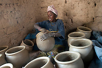 Woman working on pottery containers fo sale at local market