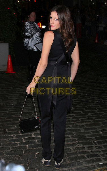 LIV TYLER .at the Grand re-opening of Chanel Soho,  New York City, NY, USA, .September 9th, 2010..full length black top ribbons back rear behind over shoulder blouse sleeveless trousers bag  brogues shoes high waisted cream beige tow tone .CAP/LNC/TOM.©LNC/Capital Pictures.