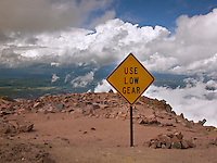 A short distance down the gravel road from the summit of Pike's Peak, near Colorado Springs, CO, a traffic sign warns to use low gear. We can see a high stratus of clouds at our approximately 14000 foot level, broken near us so that we are in sunlight. There are no guardrails, and the scene appears to be an island in the clouds. August 2006. clouds, cumulus, cumulonimbus, cloudbank, Colorado, mountains, sky, landscape, scenery, vacation, travel