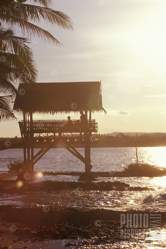 People in thatched hut on the ocean at sunset, Siargao Island, Philippines