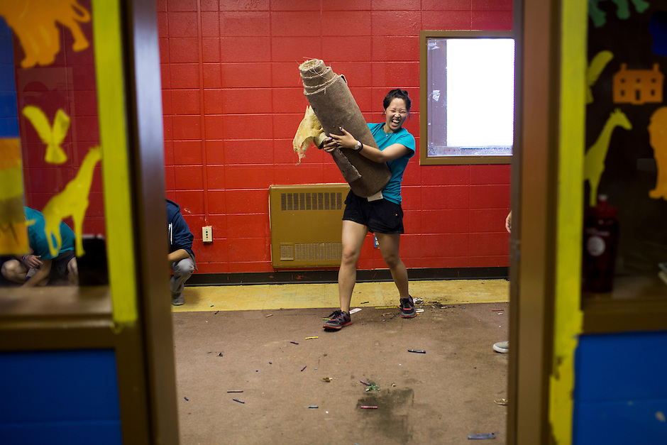"""Josephine Lukito reacts as she removes carpeting during """"Circle the City with Service,"""" the Kiwanis Circle K International's 2015 Large Scale Service Project, on Wednesday, June 24, 2015, at the Friendship Westside Center for Excellence in Indianapolis. (Photo by James Brosher)"""