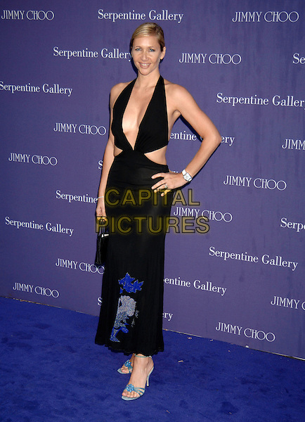 TANIA BRYER.Serpentine Gallery Summer Party.Kensington Gardens.London 30 June 2005.full length black halterneck dress cut out skin revealing hand on hip tanya blue flower pattern print.Ref: PL.www.capitalpictures.com.sales@capitalpictures.com.©Capital Pictures