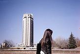 """Das """"Hotel Kasachstan"""" überragt die kasachische Metropole Almaty. Das Gebäude wurde 1970 errichtet und gilt als Wahrzeichen der Stadt. Sowjetischer Pomp und eine marode Bausubstanz erinnern die Bewohner an die Sowjetzeit, als Almaty noch Alma Ata hieß und weltweit als """"Stadt der Äpfel"""" bekannt war. Im Kreml, so heißt es, wurden ausschließlich Äpfel serviert, die an den Hängen des Tian Shan Gebirges wuchsen. Heute sind die meisten Plantagen klotzigen Neubauten gewichen. Kasachstan ist rohstoffreich und prosperiert. Kritik an den Schattenseiten des Aufstiegs duldet das System von Präsident Nursultan Nasarbajew nur geringfügig. Bilder von Hinterhöfen und grauen Vorstädten sollen nicht an die Öffentlichkeit gelangen. / Kazakhstan is a resource-rich and prosperous country.  President Nursultan Nasarbajew's system hardly allows any criticism. Pictures of backyards and suburbs are not supposed to go public."""