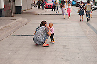 Daytime landscape view of a woman squatting with a child on a sidewalk next to a road in Bozhou in Qiáochéng Qū in Anhui Province.  © LAN