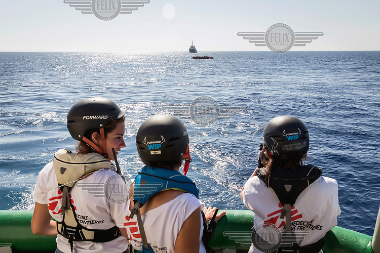 Medicins Sans Frontiere (MSF) staff on board the Bourbon Argos look on as life jackets are distributed to migrants on a inflatable raft, drifiting in the Mediterranean sea 25 nautical miles from Libya. The people were later picked up by an approaching MOAS (Migrant Offshore Aid Station) rescue vessel.