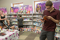 NWA Democrat-Gazette/CHARLIE KAIJO Gabriel Kurtz, 16, of Pea Ridge reads during the Scholastic Book Fair, Thursday, June 6, 2019 at the 21c Hotel in Bentonville<br />