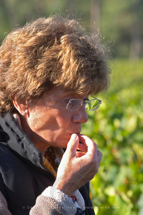 Tasting a grape to test ripeness. Martine Cazeneuve, owner. Merlot. Chateau Paloumey, Haut Medoc, Bordeaux, France.