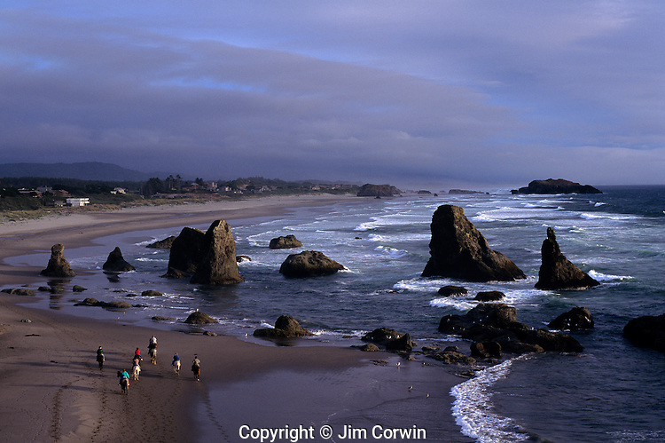 Southern Oregon Coastline sunset with people riding horses along beach at low tide Face Rock Beach Bandon Oregon State USA.