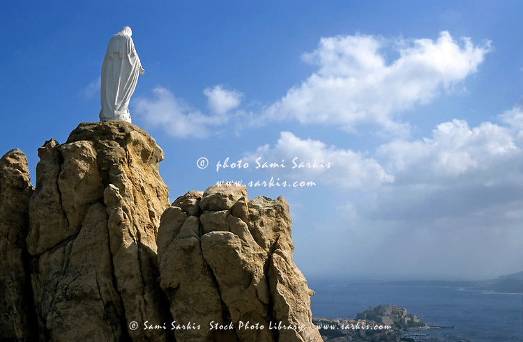 Notre Dame de la Serra statue perched on a rock above the city of Calvi, Corsica, France.