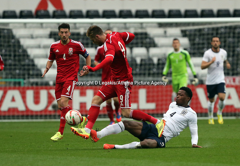Pictured: Wes Burns of Wales (C) avoids a tackle by Nat Chalobah of England. Monday 19 May 2014<br /> Re: UEFA Euro Under-21 Qualifier, Wales v England at the Liberty Stadium, Swansea, south Wales, United Kingdom