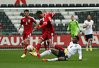 Pictured: Wes Burns of Wales (C) avoids a tackle by Nat Chalobah of England. Monday 19 May 2014<br />