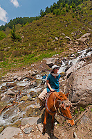 Western tourist on horseback crossing small creek, Gangabal Lake region of Kashmiri Himalayas, India.