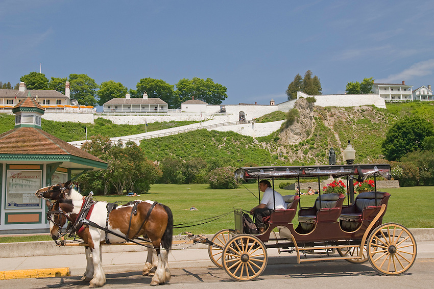 A horse-drawn carriage gives tours in front of Fort Mackinac State Park on Mackinac Island in Michigan.