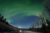 winter landscape shows Northern Lights (Aurora Borealis) in sky above Kenai Mountains inTurnagain Pass area with Seward Highway January 2014